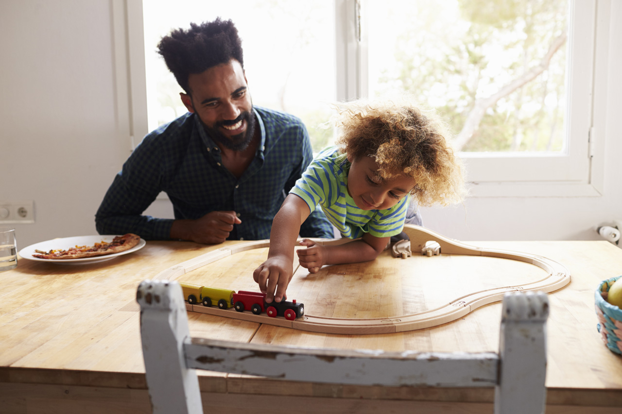 Father and son happily sit at the kitchen table playing with a train set