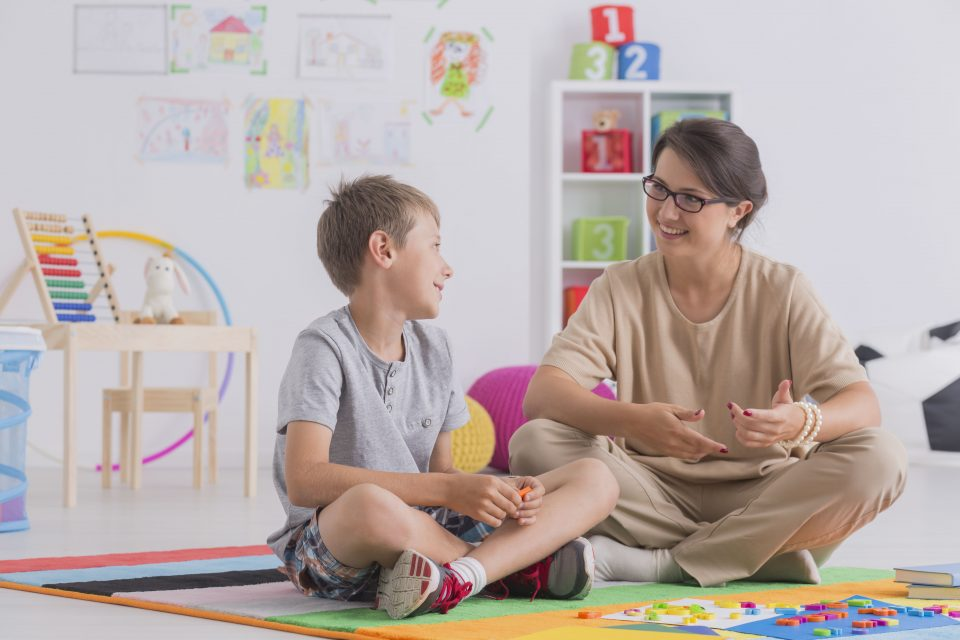 Smiling young boy and therapist sitting on floor and talking at home