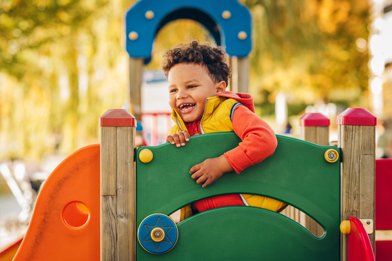 Young boy wearing a yellow vest smilies while playing on green and orange playground