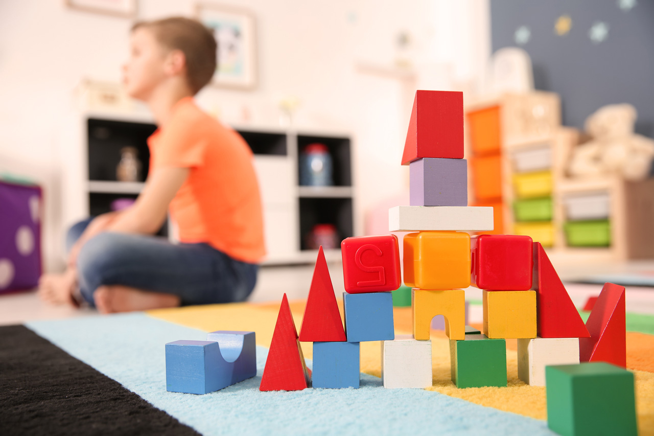 Colorful plastic and wooden blocks sitting on a blue and yellow rug with young child in the background