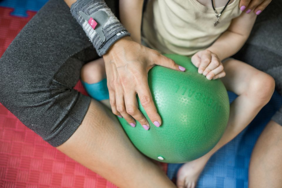 Little boy with cerebral palsy doing exercises with green ball