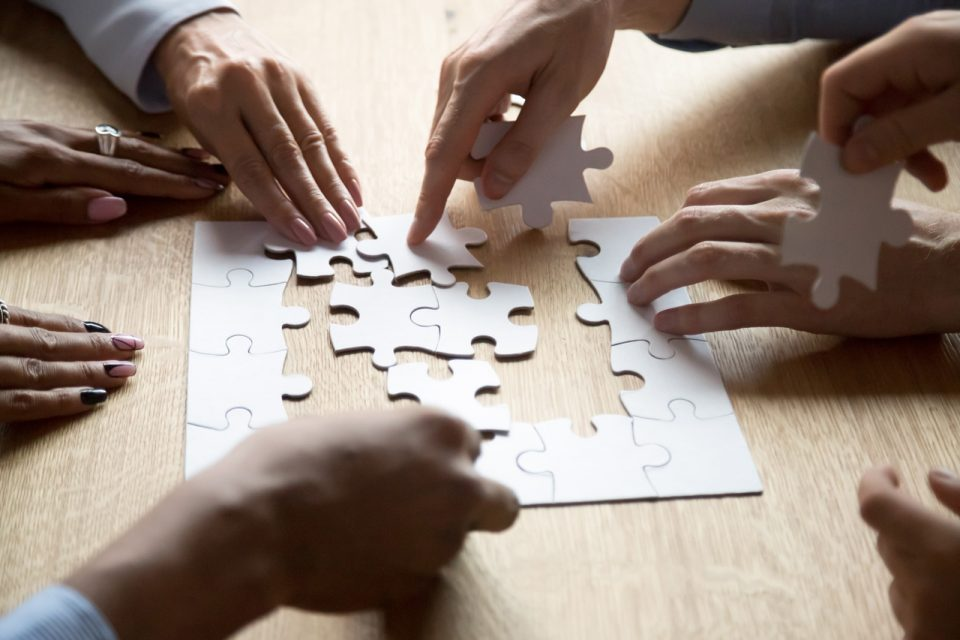 Hands of seven people sitting at wooden table putting together a puzzle