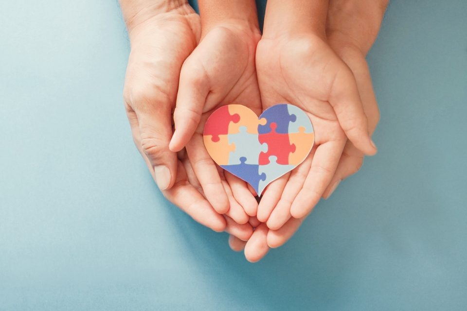 Women and child with hands laying inside of one another hold a colorful heart made out of puzzle pieces