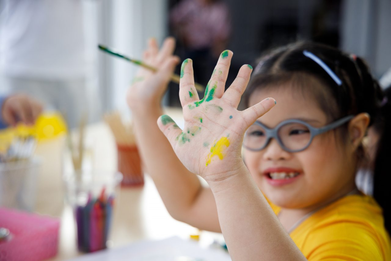 Asian girl in yellow shirt with Down's syndrome painting her hand.