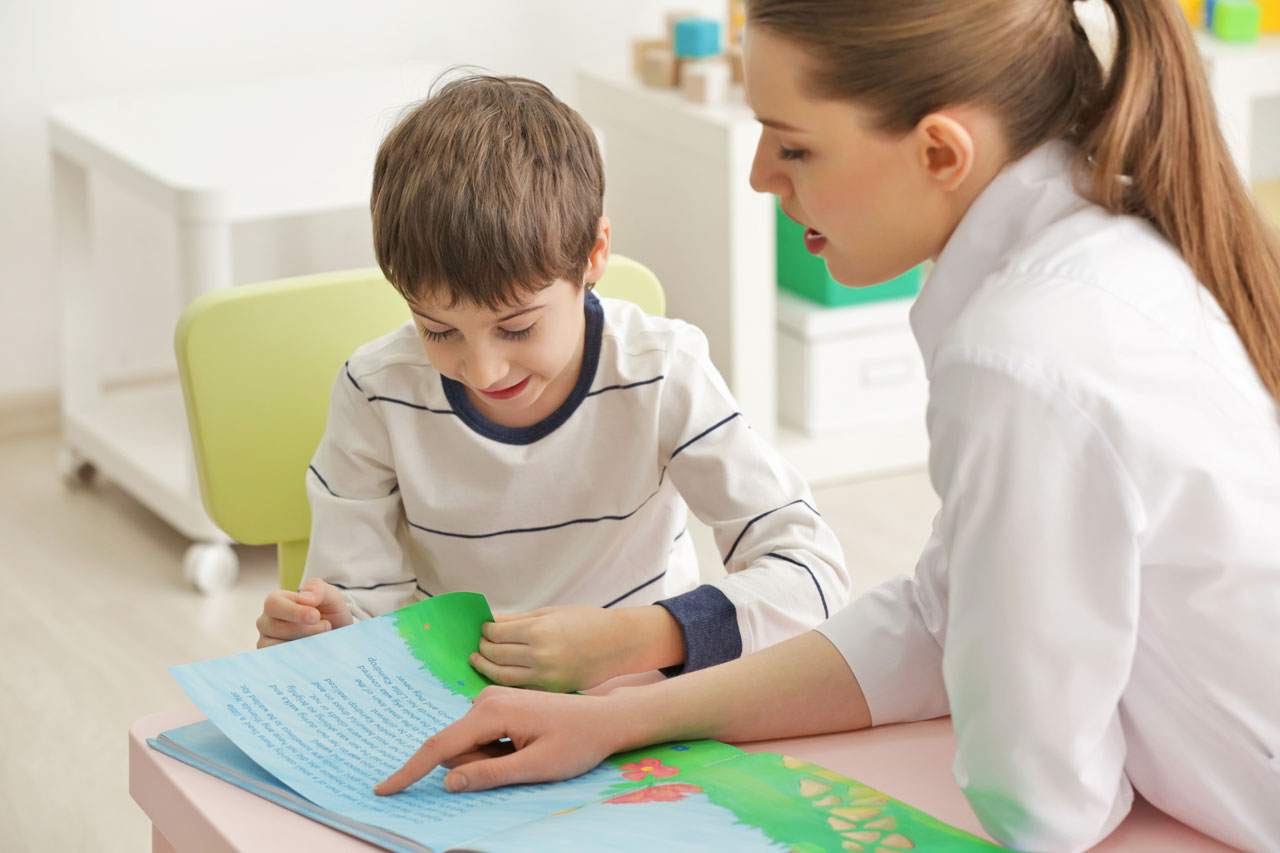little boy reads book while clinician assesses