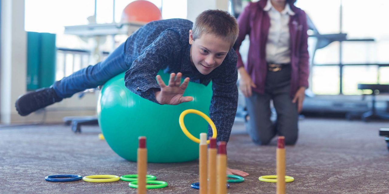 adolescent boy in blue button up shirt laying across large teal exercise ball tossing plastic yellow ring onto ring toss for occupational therapy