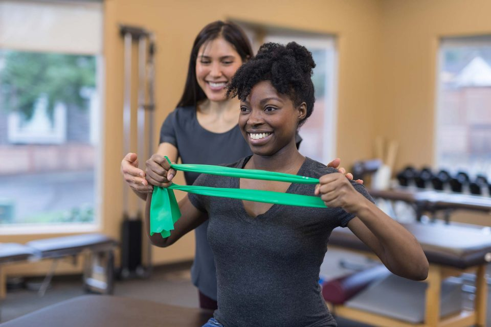 Smiling physical therapist of Asian descent works with her patient, a young African American woman. They are doing a stretching exercise with a flexible green resistance band