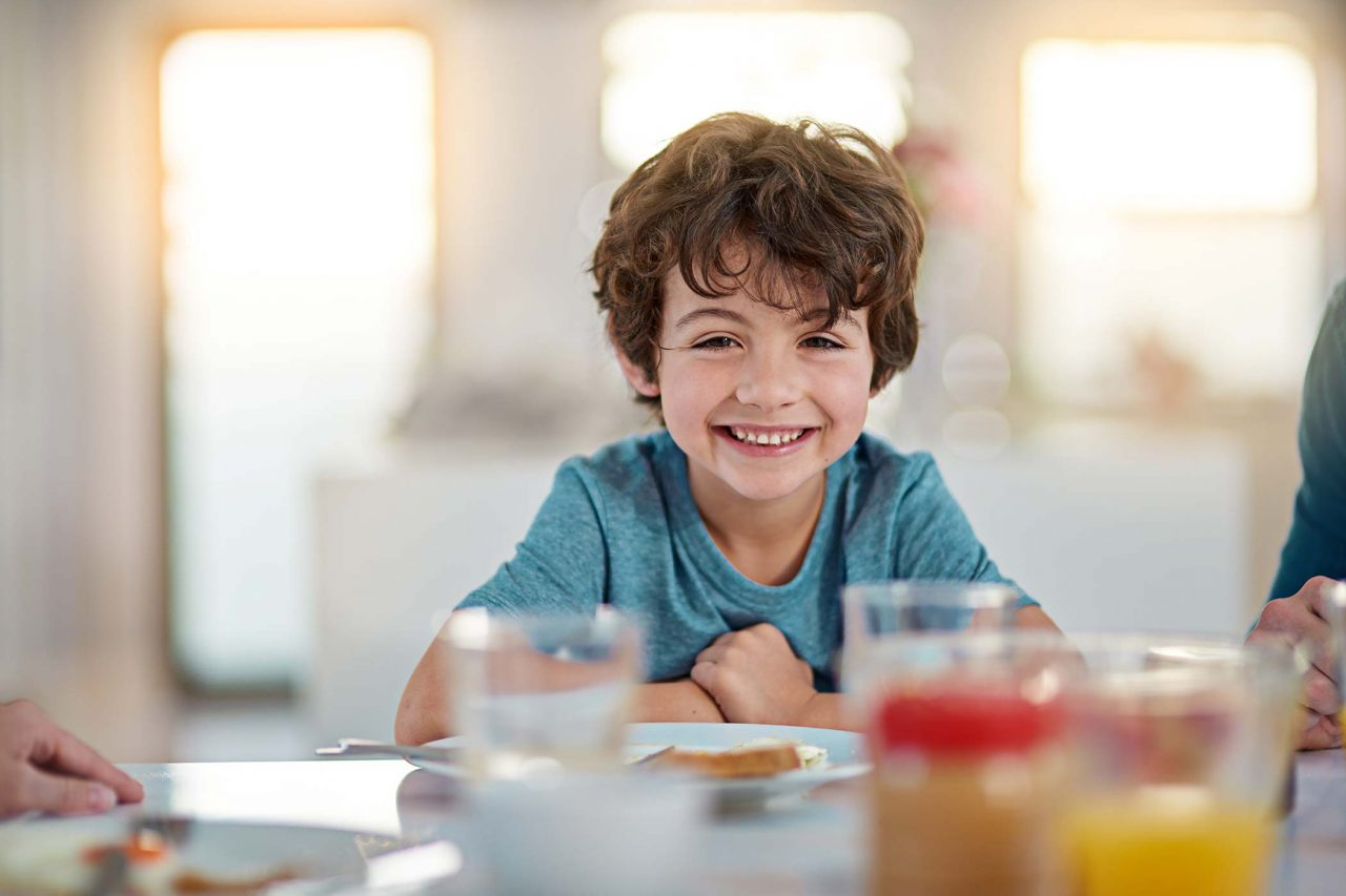 young boy in teal crew neck with tousled brown hair smiles over breakfast