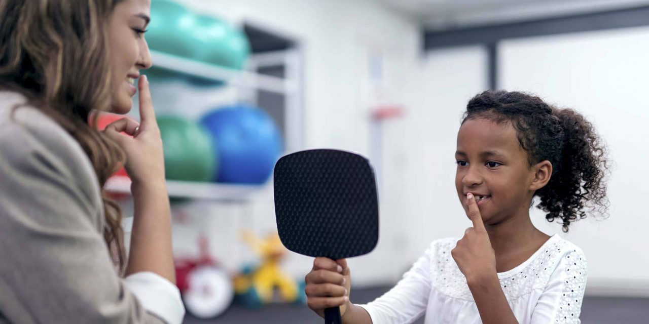 Therapist demonstrates putting index finger to lips as young brown skinned girl in a white top holds up a hand mirror with one hand and copies the gesture with her other hand while looking at her reflection