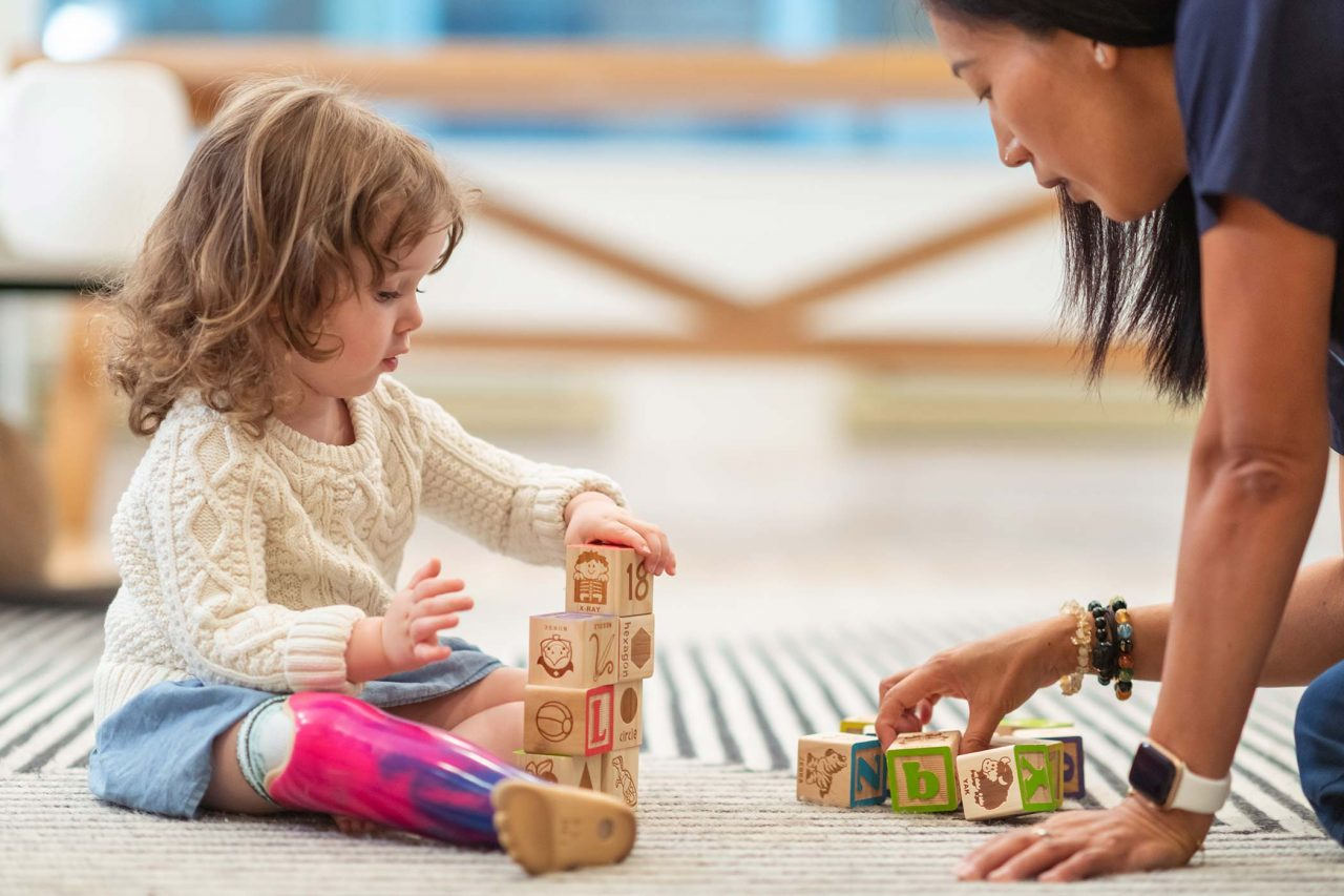 curly haired toddler in a cream colored sweater with a purple and pink tie-died prosthetic leg stacks blocks printed with the alphabet on the carpet with therapist in navy scrubs
