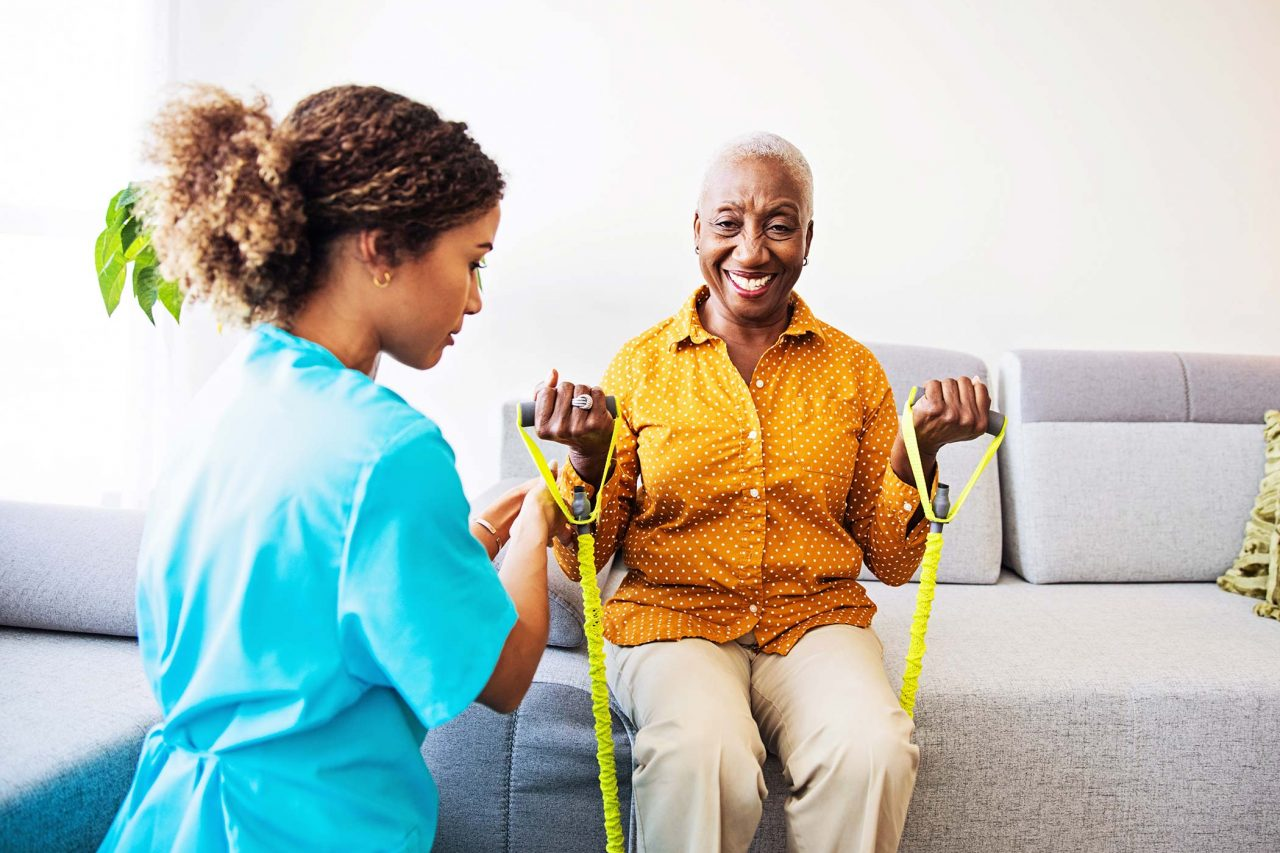 physical therapist in light blue scrubs assists elderly woman with arm strength exercises on couch at home