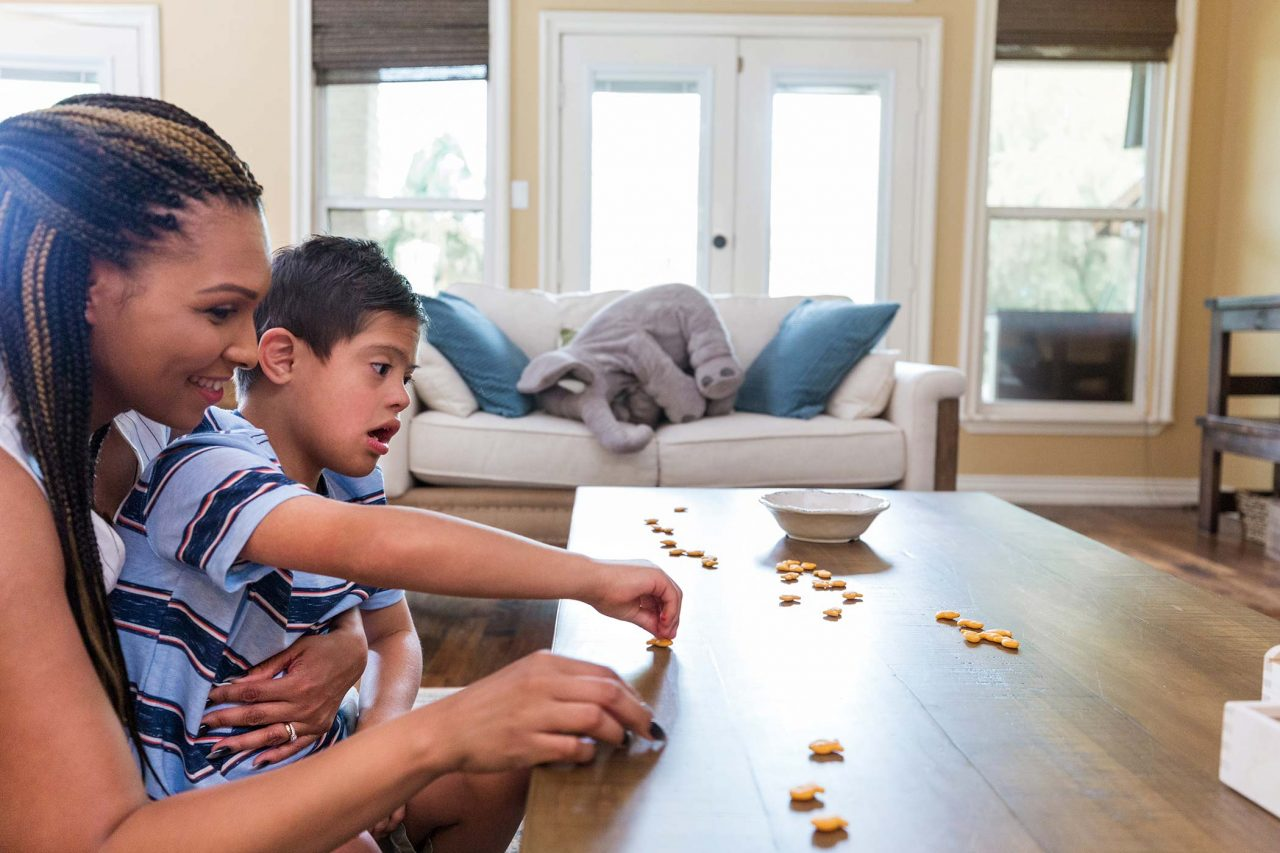 young mom and boy with down syndrome count out goldfish crackers on wooden coffee table