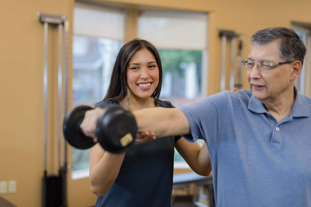 older male patient holds dumbbell straight out from body with help from physical therapist