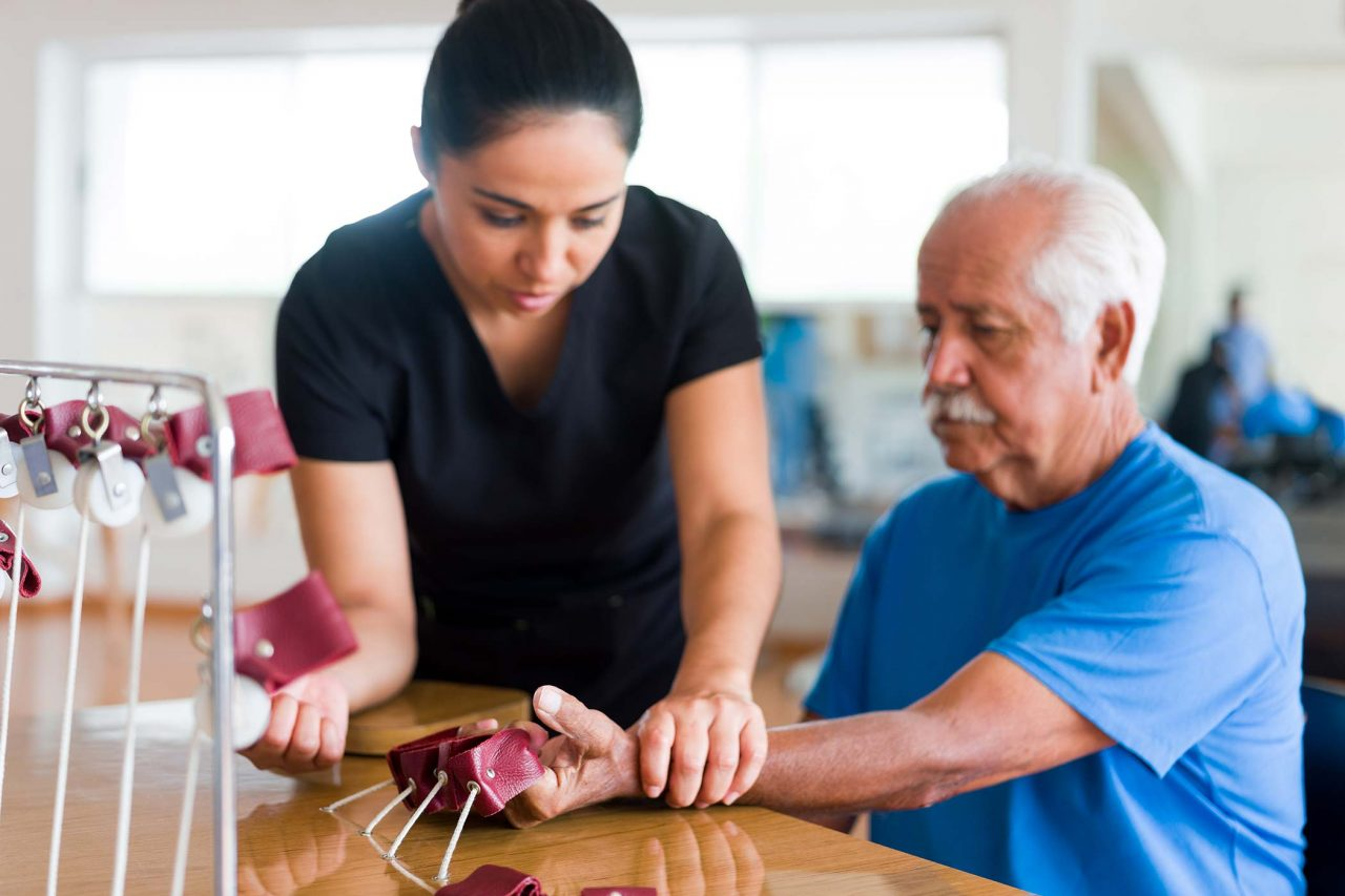 senior male patient sitting and exercising his hand with a physical therapy device next to a occupational therapist