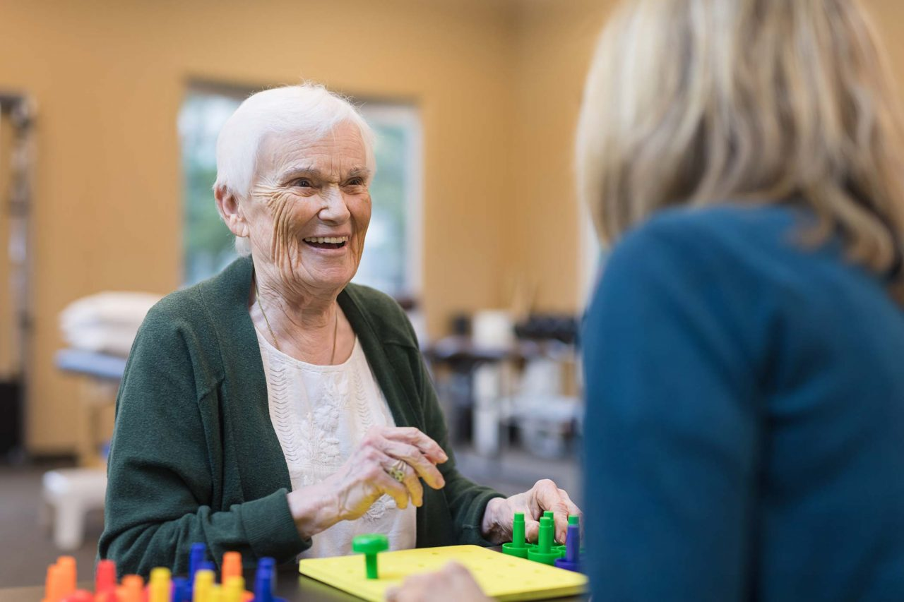 Occupational therapist works with smiling senior woman in green cardigan and white floral embroidered shirt