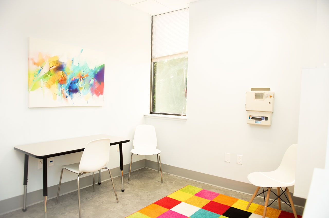 Carolina Therapeutics white office space with desk, chairs and bright colorful rug