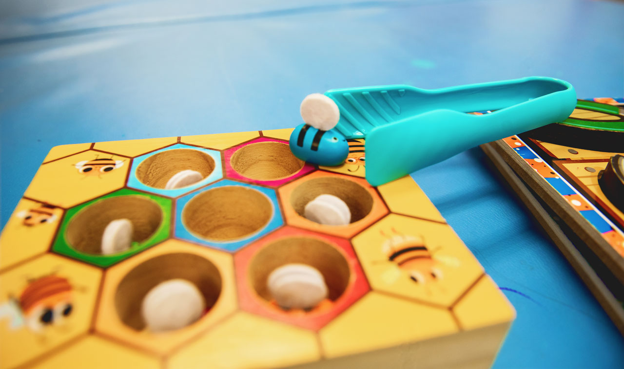 small wooden game emulating a honeycomb with bees and a set of plastic blue tweezers at Carolina Therapeutics Fort Mill SC office