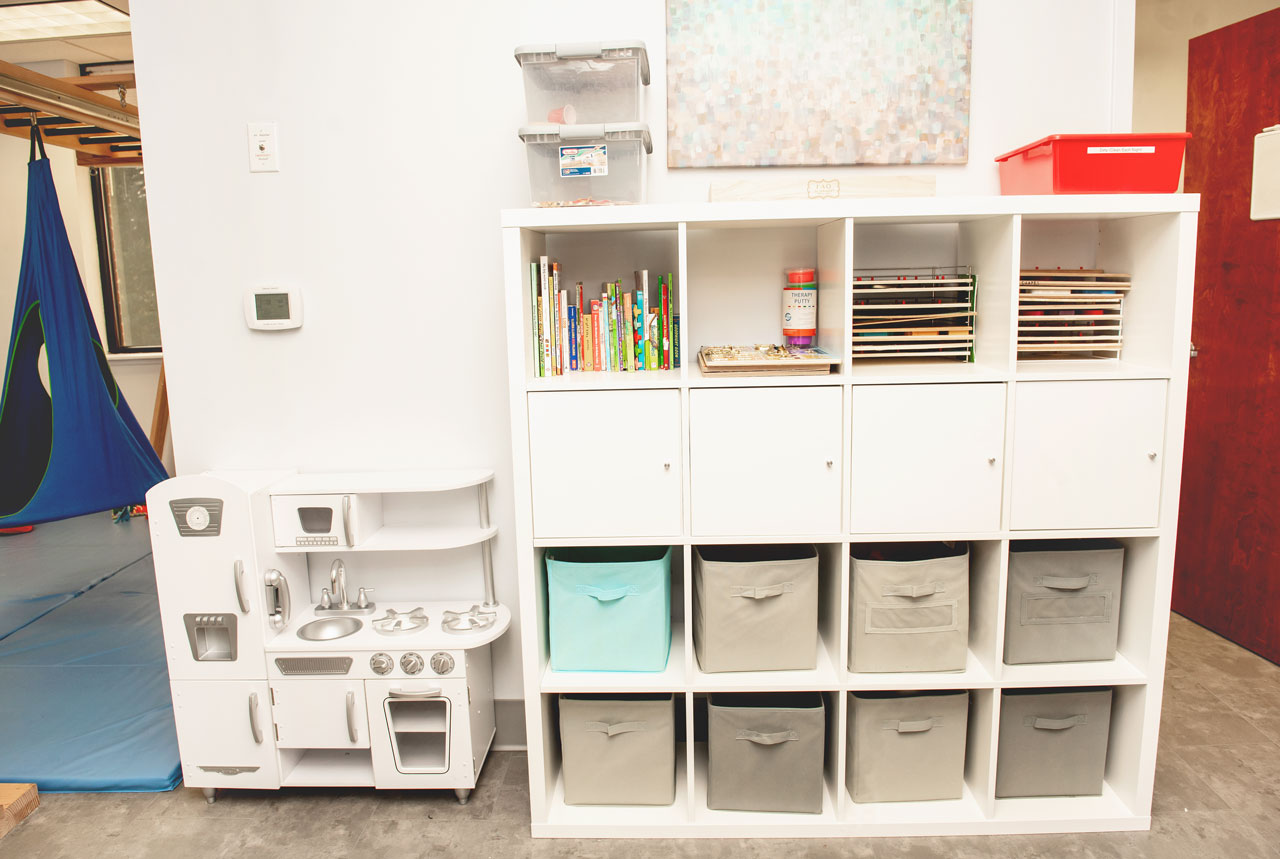child's play kitchen and tidy storage cabinet with books and fabric bins at Carolina Therapeutic Fort Mill SC office