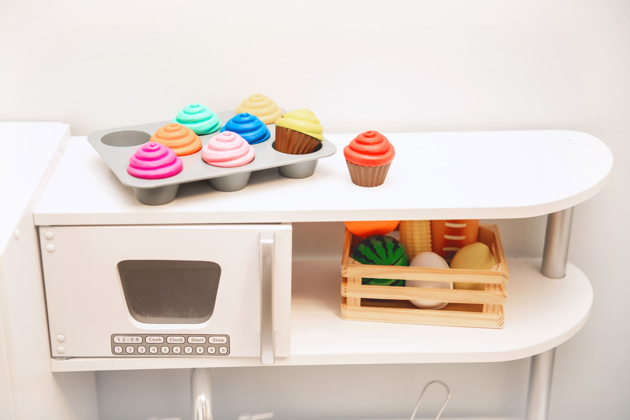 plastic baking sheet of plastic cupcakes and plastic basket of plastic grocery items on play table at Carolina Therapeutics Fort Mill SC office
