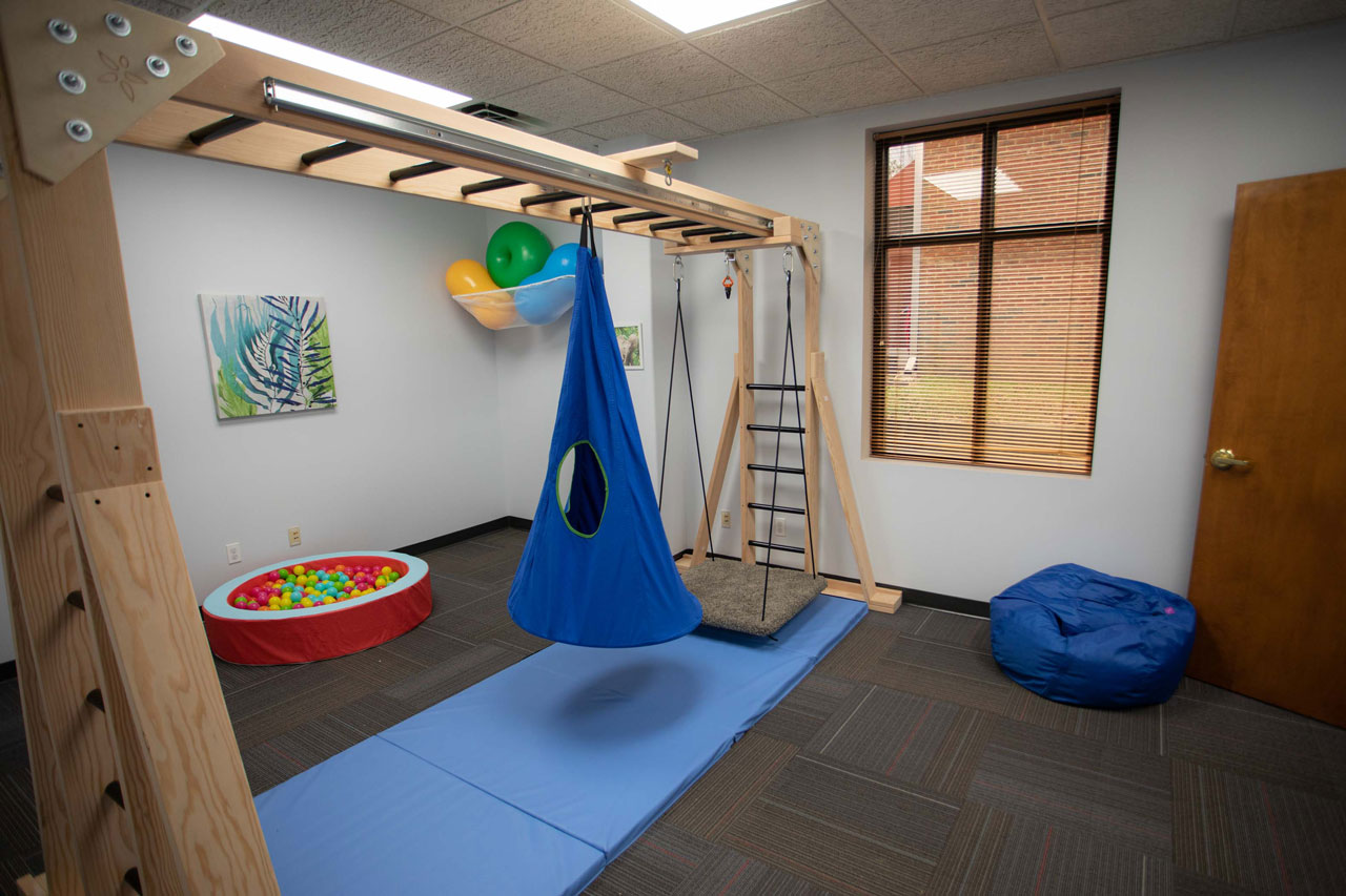 Child focused occupational therapy space with blue bean bag, mats and colorful balls.