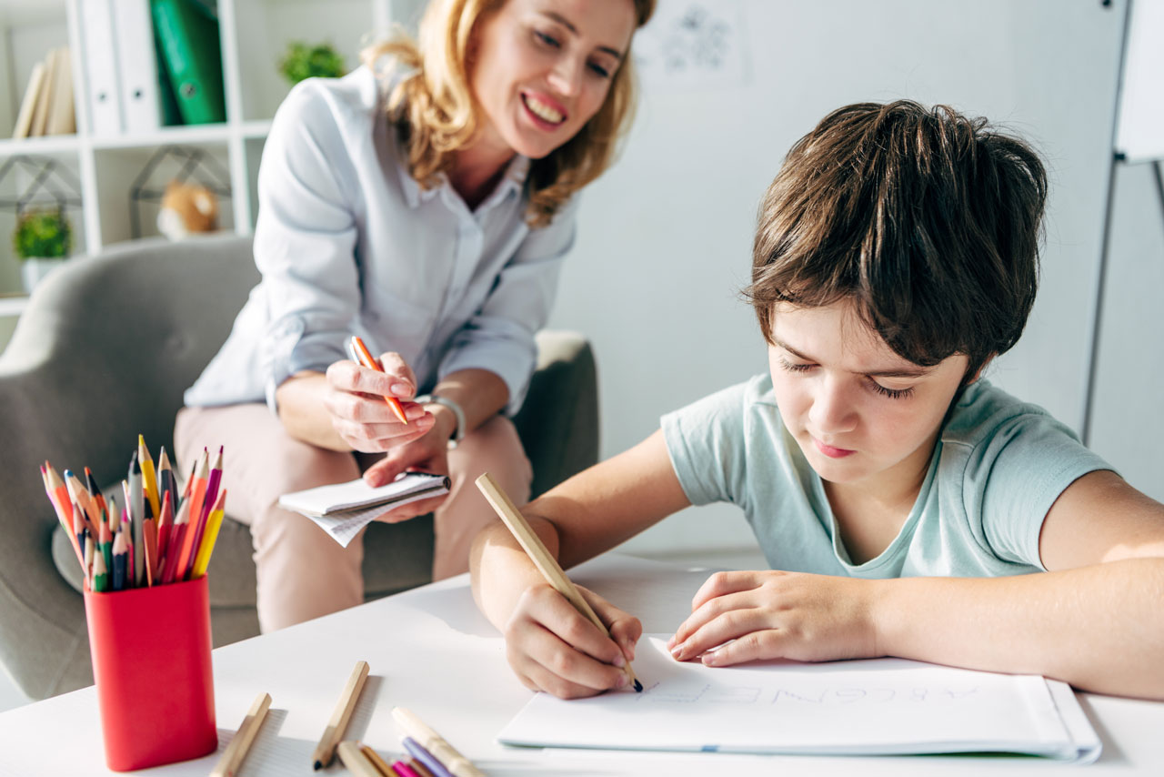 kid drawing on paper with pencil and clinician assessing